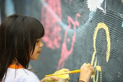 Young girl paints the  wall, outside
