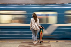 Young girl passenger with longboard standing on subway station platform with blurry moving blue train on background, rear view. Woman with skateboard watching metro pass fast at the station.