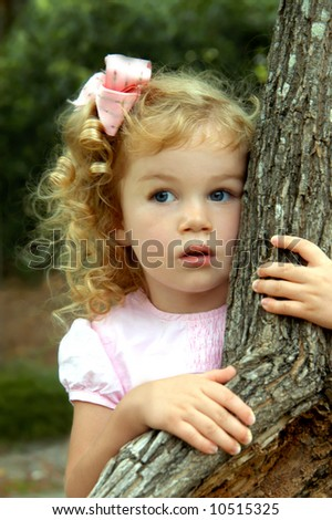 Young girl peeks out from behind a tree.  She has golden curls and a pink bow.