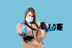 Young girl photographer with photo-video cameras on with protective gloves and a medical mask shows the class on a blue background. High quality photo