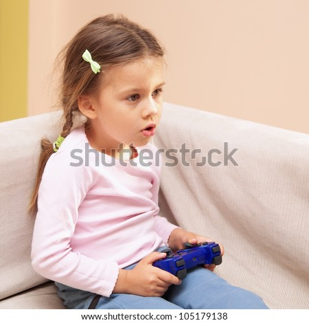 Young girl playing a video game with a blue controller