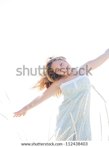 Young girl playing airplanes with her arms open against the sky, smiling.