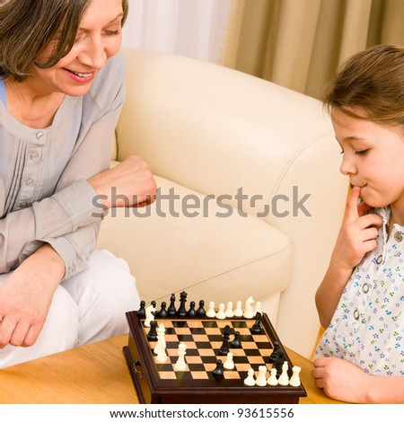 Young girl playing chess with grandmother together at home - stock photo