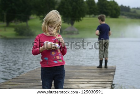 Young girl playing computer game in nature