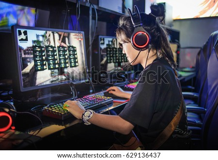 young girl playing computer games in internet cafe