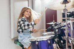 young girl playing drums in music studio