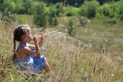 young girl playing flute on the hill