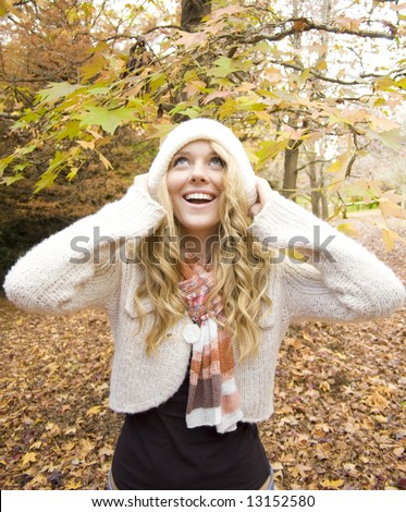 Young girl playing in the Autumn fall leaves - stock photo