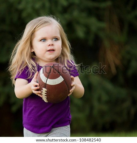 Young girl playing in the backyard running with her football
