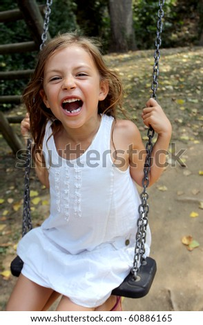 Young girl playing on a swing in a park