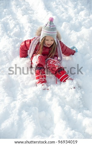 Young girl playing on the snow.