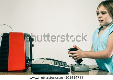 Young girl playing on vintage gaming rig in front of red television set, frustrated