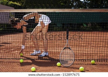 Young girl playing tennis on court, outside