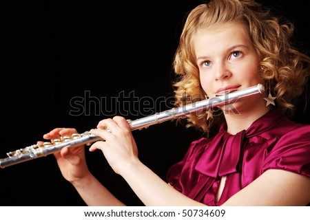 young girl playing the flute on a black background