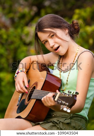 Young girl playing the guitar and singing outdoors