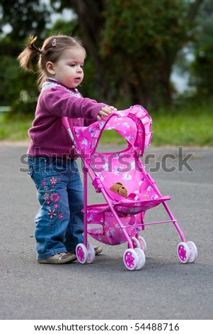 Young girl playing with a pram
