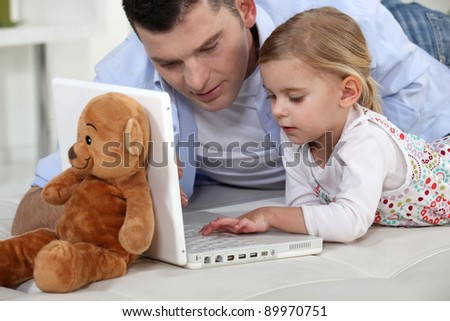 Young girl playing with her father's laptop