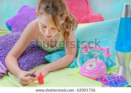 Young girl polishing nails in room