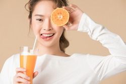 Young girl poses with apple juice and fresh orange cut into half portrait isolated on brown background