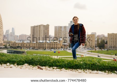 young girl posing against the backdrop of the city and beautiful architecture