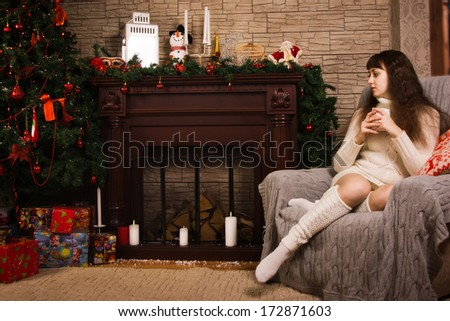 Young girl posing by the fireplace with Christmas gifts