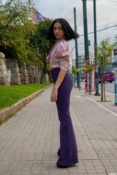 Young girl posing in purple outfit in center of athens greece.