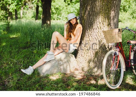 young girl posing in the park with bicycle