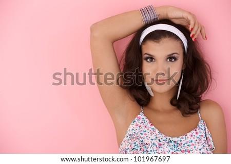 Young girl posing over pink wall, looking at camera. #101967697