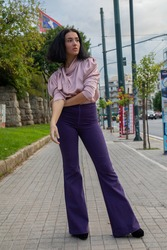 Young girl posing with purple outfit on street at athens greece.