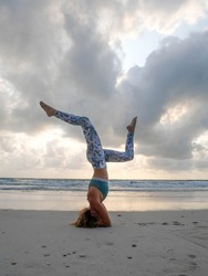 Young girl practice headstand yoga pose at seaside at sunset. Vertical photo.