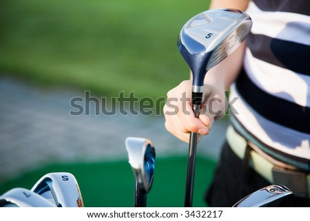 Young girl practicing golf at the range