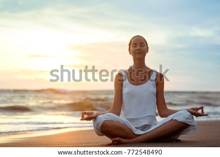 Young girl practicing yoga on the beach #772548490