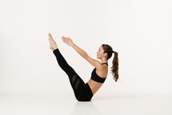 Young girl practicing yoga. Yoga on a white background. Girl in yoga asana. A girl performs yoga in a white studio