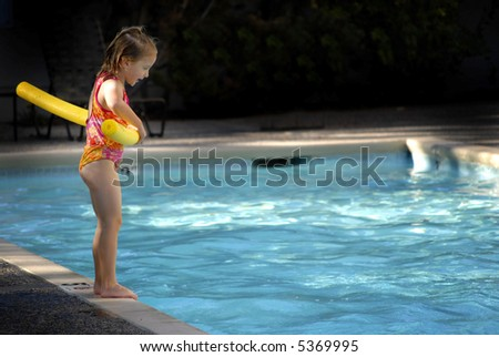 Young girl preparing to jump into a swimming pool