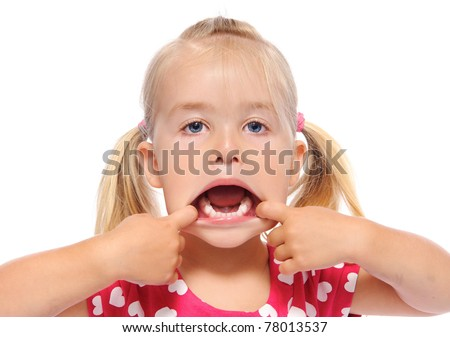 young girl pulls her mouth open and shows teeth