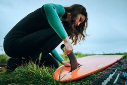 young girl putting a surfboard fin into a surf longboard. Lifestyle and vacation concept.