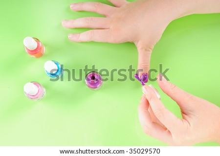 Young girl putting on own purple nail polish