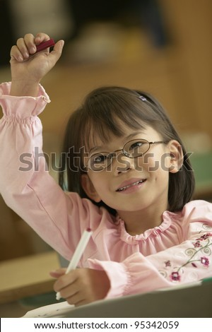 Young girl raising her hand in class