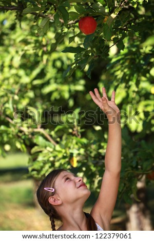 Young girl reaching up for an apple under an apple tree