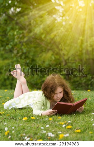Young girl reading a book outdoors in summertime