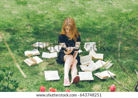 Young girl reading a book while lying in the grass. A girl sits among the many books in the garden. Many books on the grass in the summer garden