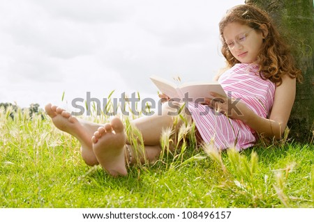 Young girl reading a book while sitting under a tree in the park, smiling.