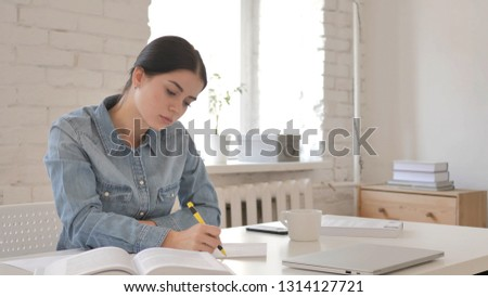 Young Girl Reading Book and Writing on Paper, Contract #1314127721
