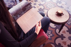 Young girl reading book in cafe with coffee on her table top view.Young woman reading magazine in cafe.