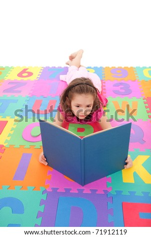Young girl reading book on alphabet floor mat. Isolated on white.