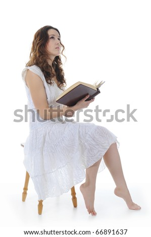 young girl reading book sitting on a stool in a bright room. Isolated on white background