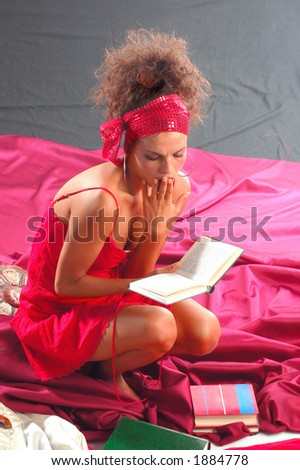 Young girl reading books on her bed