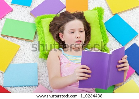 Young girl reading - surrounded by lots of colorful books