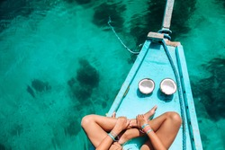 Young girl relaxing on the boat and eating coconut over clear sea water, top view. Travelling tour in Asia: El Nido, Palawan, Philippines.