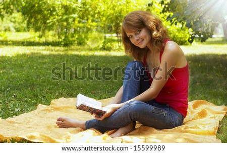 young girl reposes in park with book